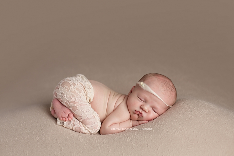 Newborn girl wearing lace pants and headband in peach MN