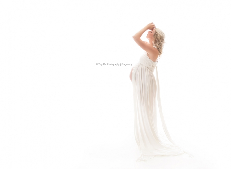 Pregnant woman in white gown professional photographer MN