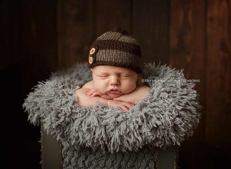 Newborn boy wearing brown hat in metal basket