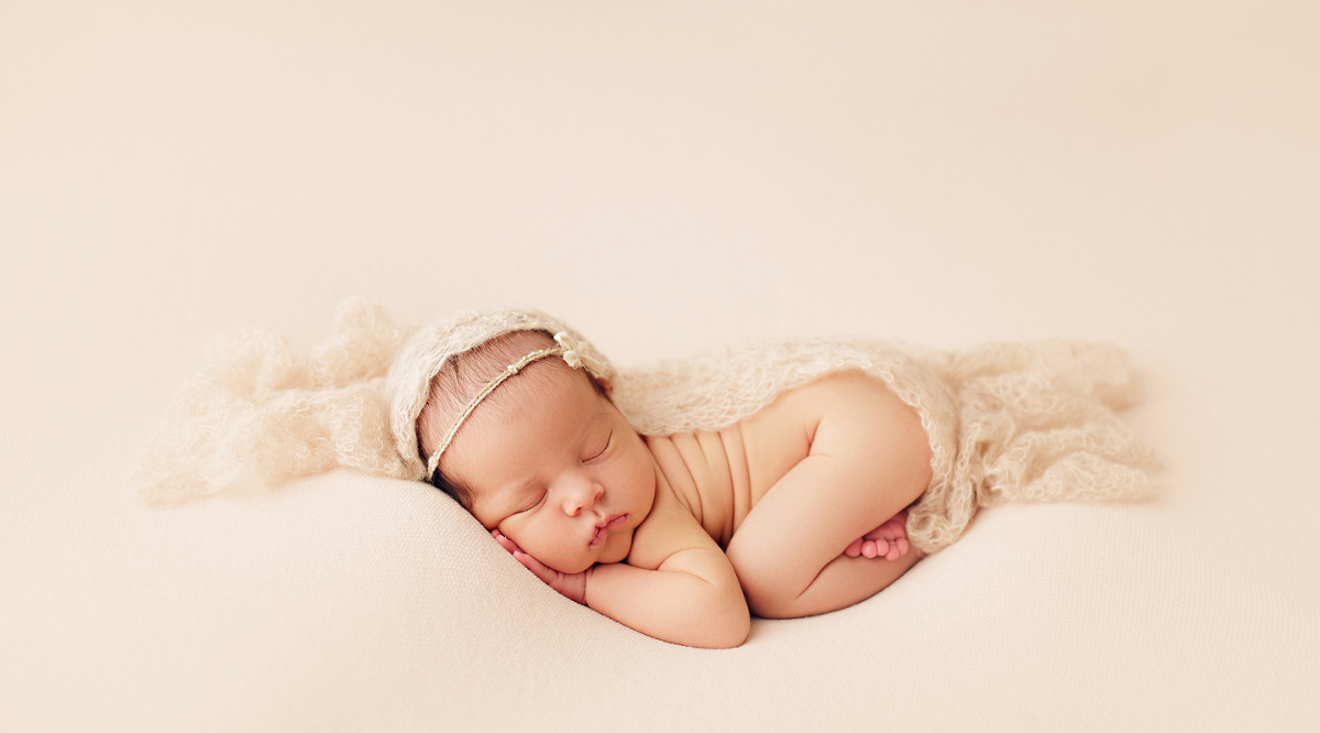 Newborn baby girl laying on tummy with blanket wrapped over her