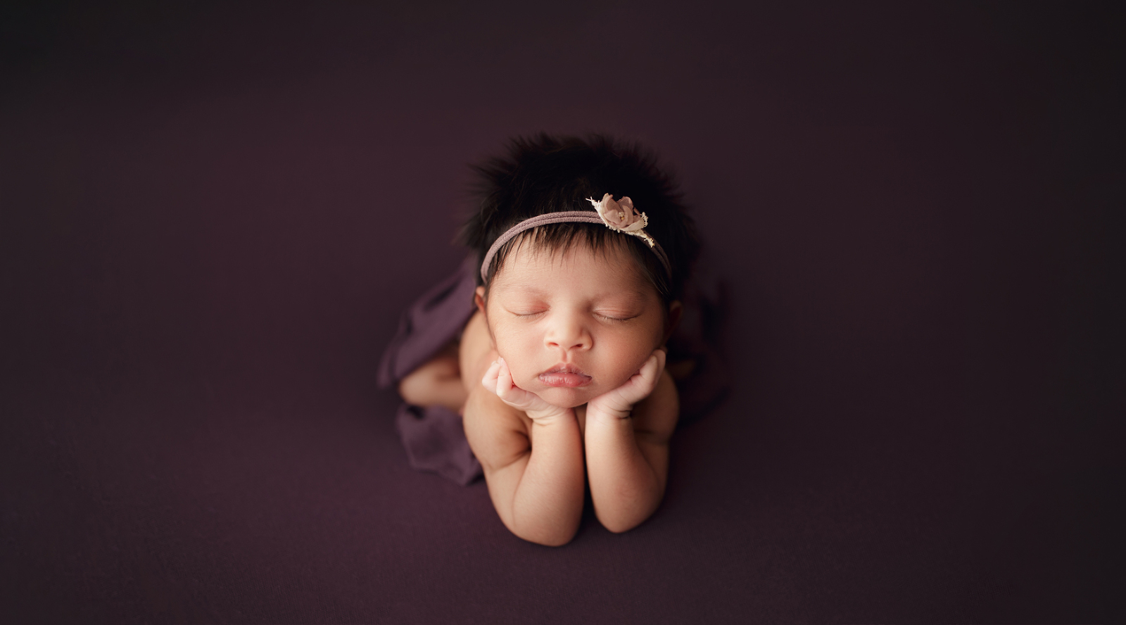 Newborn girl with lots of hair wearing a purple headband resting her chin on her hands