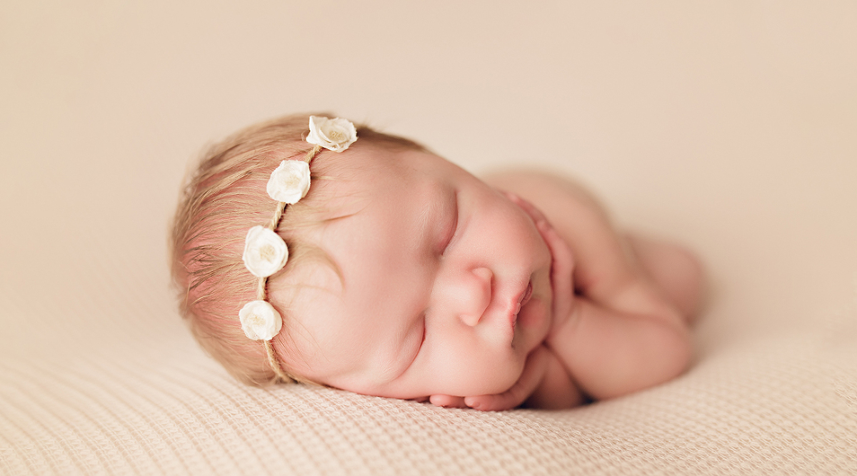 newborn baby girl with blond hair wearing white floral headband