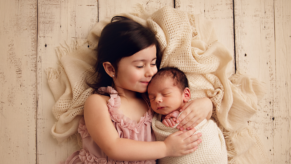 Big sister in pink dress laying down holding her baby brother
