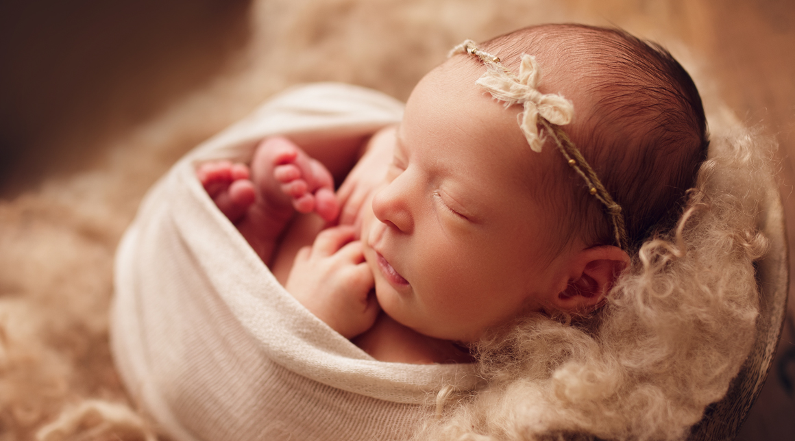 Side view of a newborn girl wrapped up wearing a bow headband