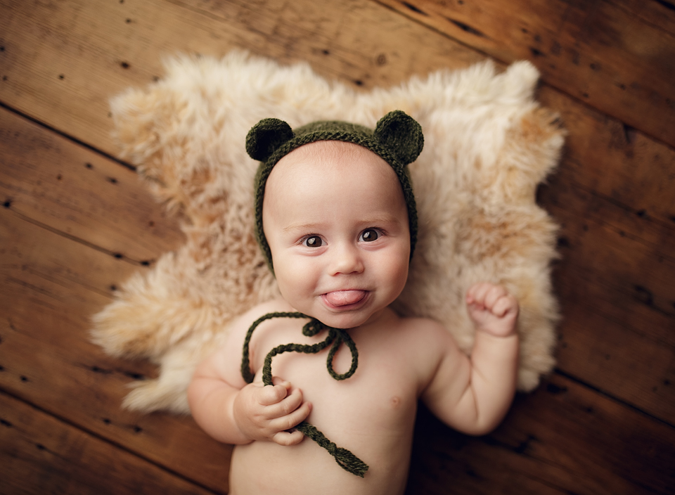 6 month old baby boy laying on fur wearing green bear hat while sticking tongue out