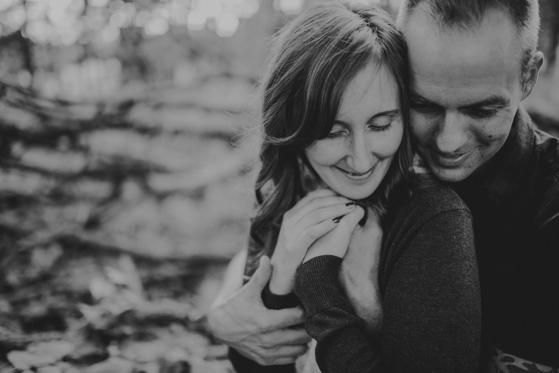 Black and white photo of a husband hugging his wife from behind
