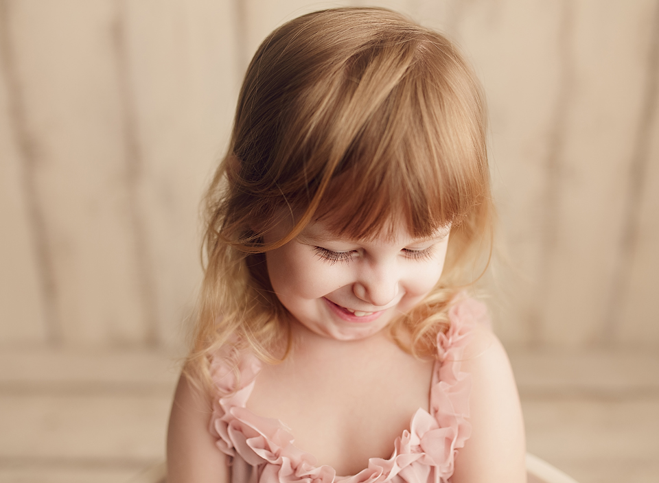 toddler girl in pink dress looking down and smiling