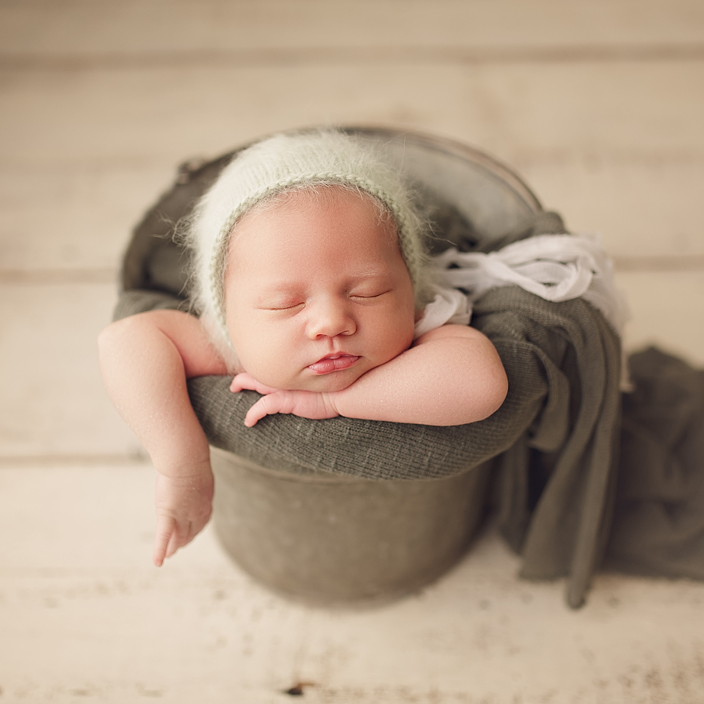 Newborn girl in metal bucket wearing green angora bonnet