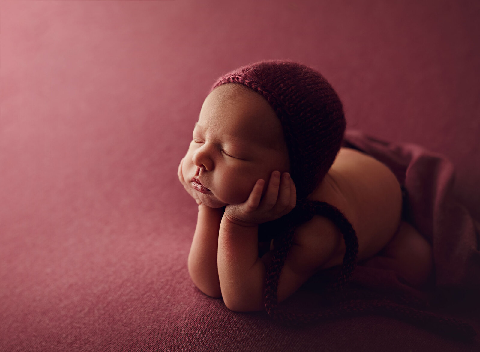 Newborn girl resting with chin in hands