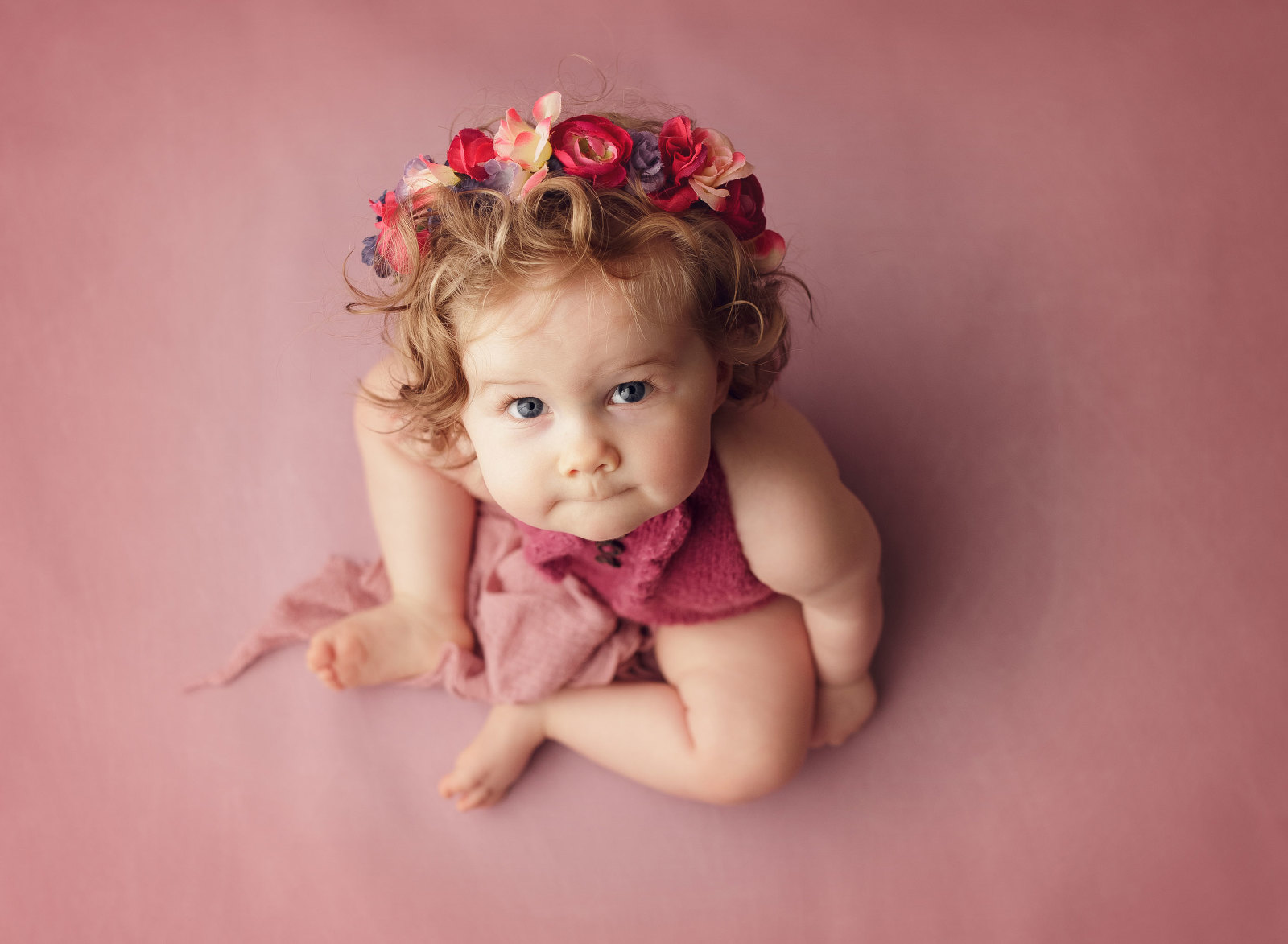 One year old girl sitting on floor wearing floral crown looking up